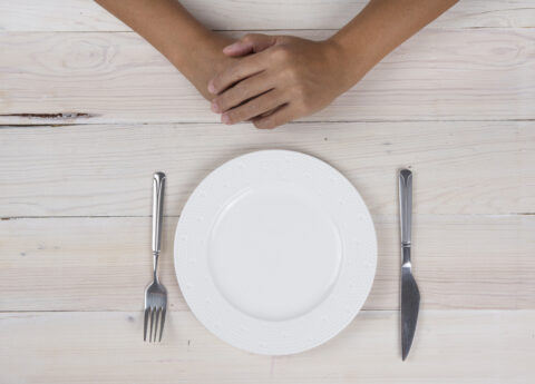 Folded hands and empty plate